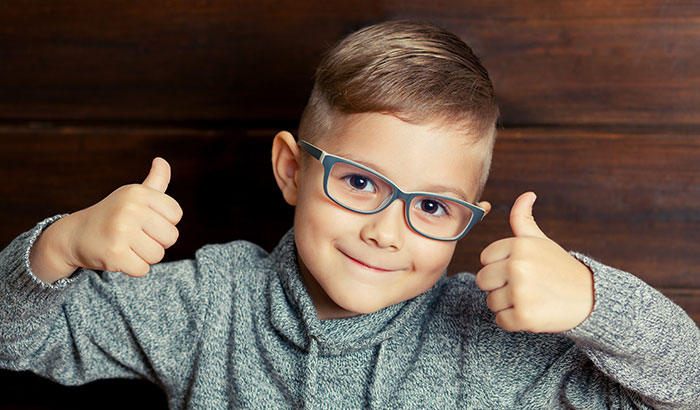 young boy child pediatric happy wearing glasses thumbs up