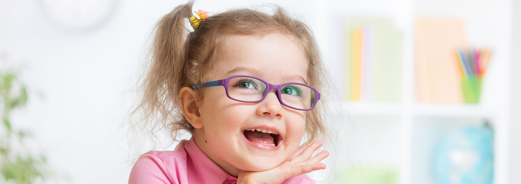 White pediatric girl wearing purple glasses smiling