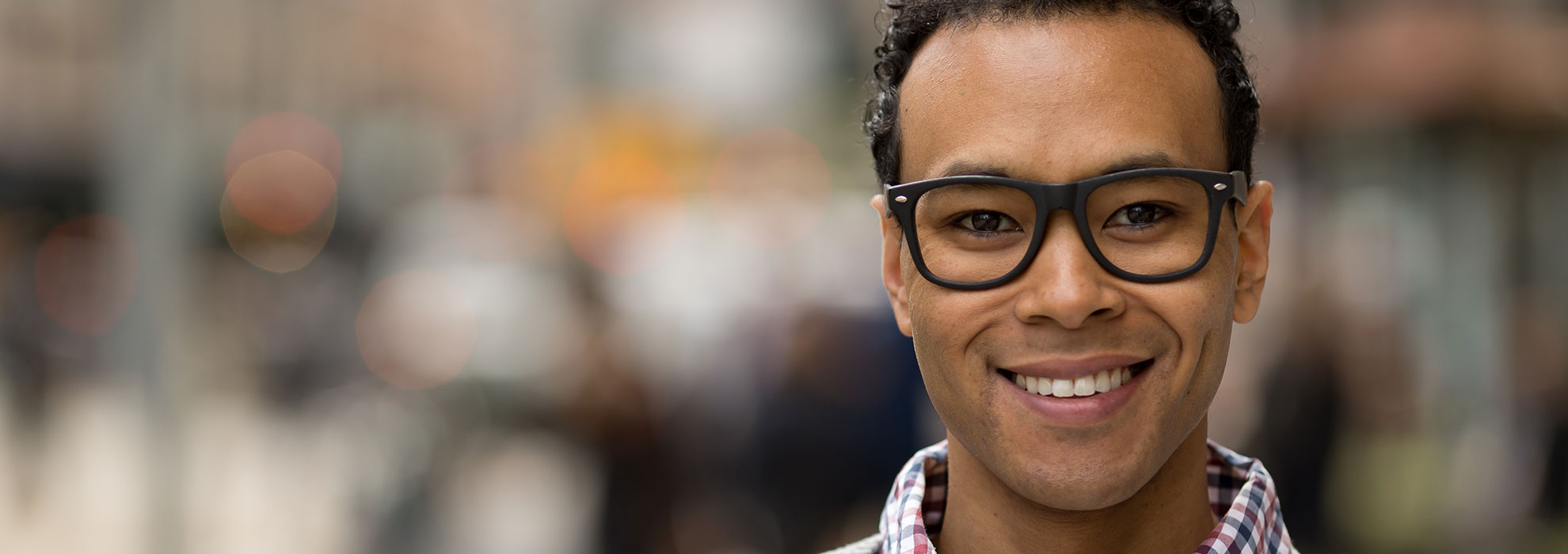 Black male smiling wearing thick glasses