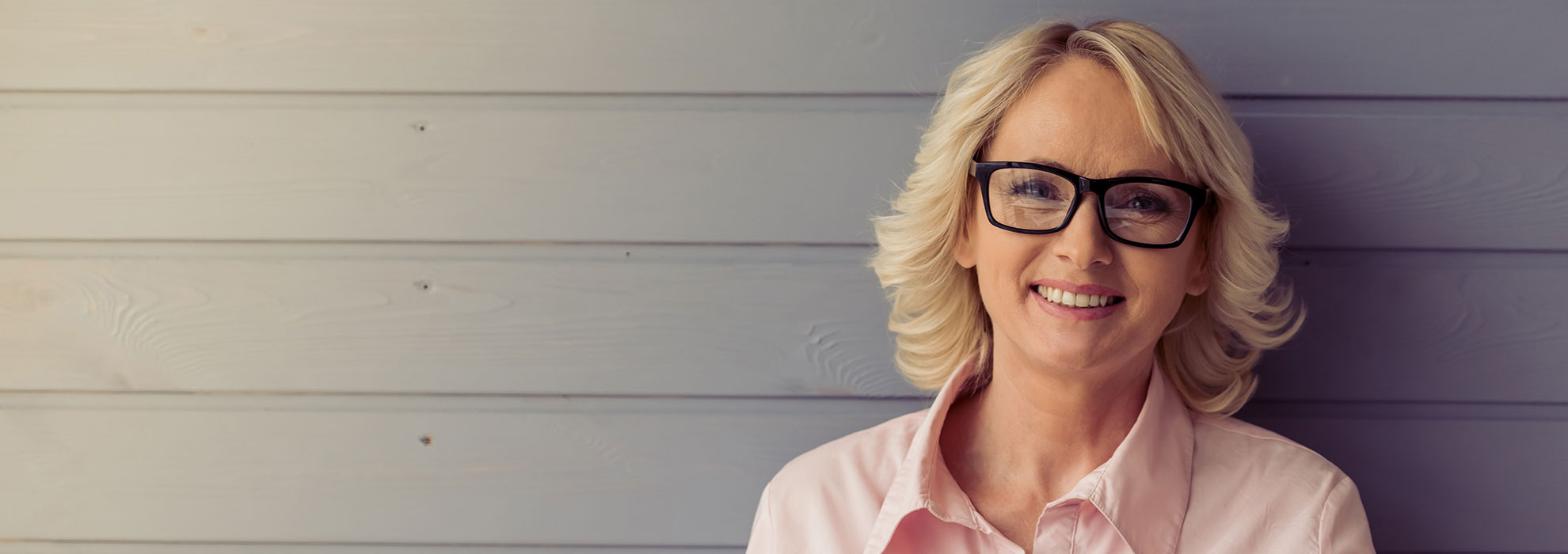 White female wearing pink shirt and glasses against gray wall