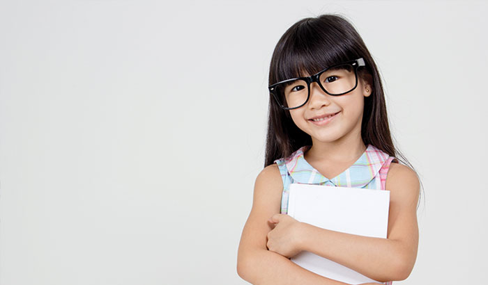 Young pediatric girl wearing glasses holding school books